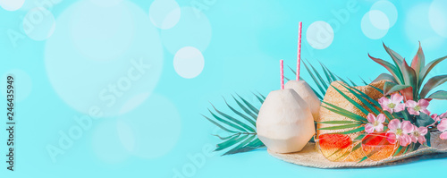 Beach accessories with fresh coconut, drinking straws and tropical leaves and flowers , sunglasses and straw hat on sunny blue background with bokeh. Summer holiday concept, banner. - 246435949