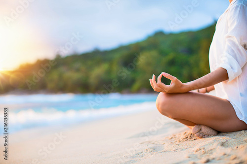 Foto Murales Closeup of Woman's Practicing Lotus Pose on the Beach at Sunset