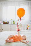 Baby girl in orange romper with colorful balloon - 246450792