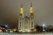 Scenic view of cathedral of Ottawa (Notre-Dame de Ottawa) in capital of Canada. Depressive beautiful winter look of old historic famous catholic temple covered by snow in nighttime illumiantion
