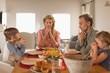 Leinwandbild Motiv Family praying before having food on dining table