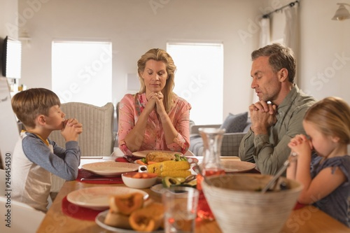 Family praying before having food on dining table - 246454530