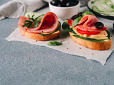Fresh sandwich with ham, cheese, cucumber, olives and basil leaves ready-to-eat. Slice crust baguette bread with perfect ham on gray stone background. Copy space for text