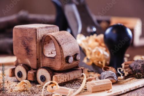 fototapeta na ścianę Wooden toy truck van car on the carpentry workbench. Hobby diy crafts, making
