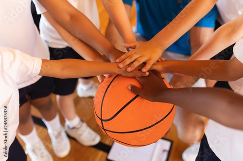 Leinwanddruck Bild Close-up of Schoolkids forming hand stack on basketball at