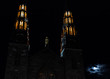 Close up of cathedral spires at night next to the moon in Winter