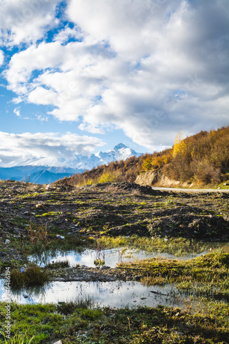 Empty road in the mountains of Svaneti region, Georgia. Snow peaks of Caucasus Mountains on a sunny autumn day. - 246486194