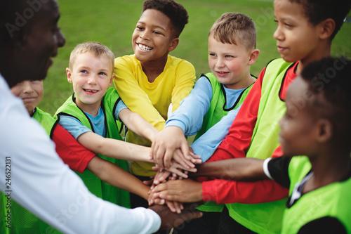 Leinwandbild Motiv Junior football team stacking hands before a match