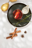 Delicious spicy hot mulled red wine with cinnamon, star anise and slice pear served in a carafe and glass for a cold winter evening or festive Christmas beverage - 246534759