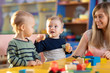 Leinwandbild Motiv Nursery babies kids playing with teacher in kindergarten