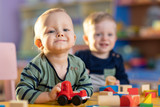 Happy smiling babies kids are playing with educational toys in nursery - 246549541