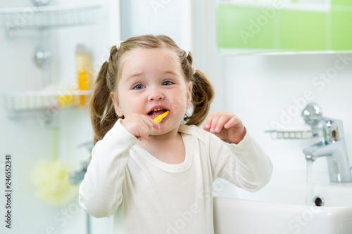 Leinwandbild Motiv funny cute child girl brushing her teeth in bathroom