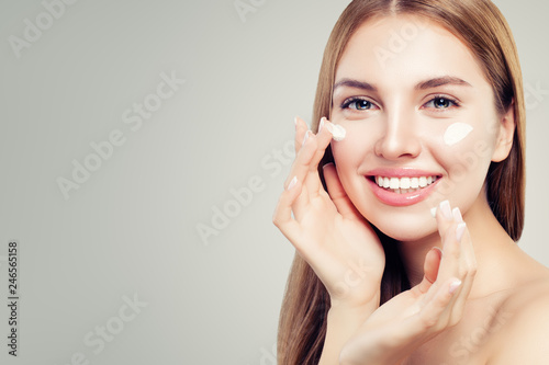 Exited beautiful woman with healthy clear skin applying moisturizing cream on her face, closeup portrait. Skin care, beauty and facial treatment concept - 246565158