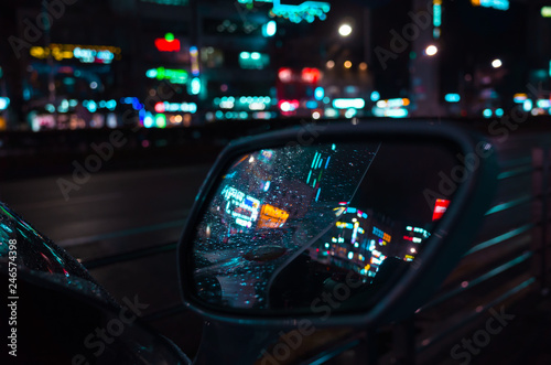 Raindrops on wet car mirror at night - 246574398
