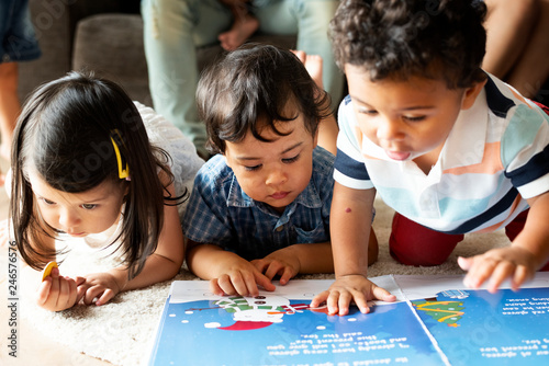 Leinwandbild Motiv Children reading a book on the floor