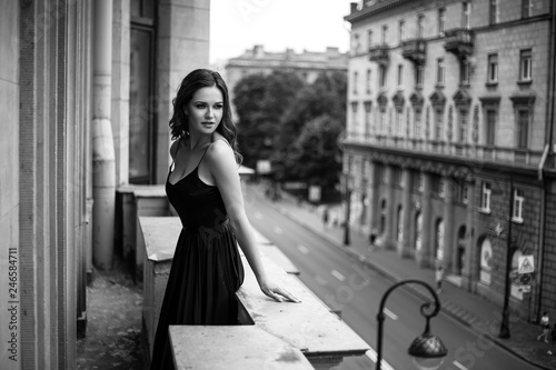 fototapeta na ścianę Black white portrait of young woman in elegant silk black dress lookingto a city from a balcony, fashion beauty photo