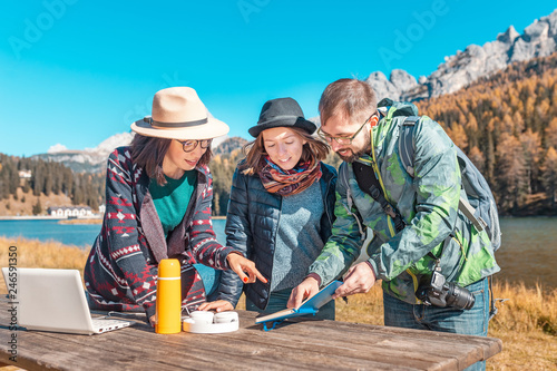 Leinwanddruck Bild Three happy friends with notebook and laptop in nature park at the background of a mountain lake in Alps