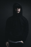 young cool rapper with black hoodie and cap standing in front of grey background