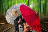 Fototapeta Bambus - Couple with traditional japanese umbrellas posing at bamboo forest in Arashiyama © Patryk Kosmider