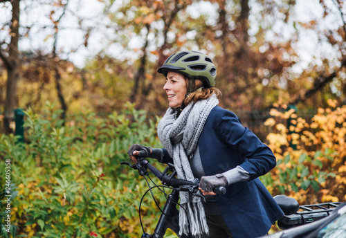Leinwanddruck Bild Active senior woman with electrobike cycling outdoors in park.