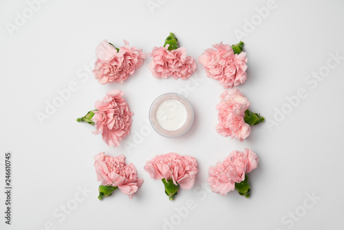 Foto Murales Flat lay of carnations flowers in square arranging and cream container on white background