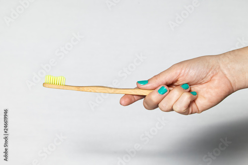 Bamboo Toothbrush in a hand isolated on grey