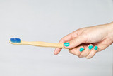 Bamboo toothbrush in a hand isolated on grey background