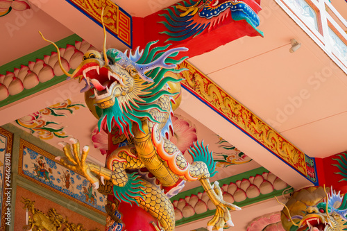 Colorful statue of Chinese dragon wrapped around the pillar. Beautiful statue of dragon carved around temple pole in Chinese public temple.