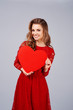Leinwanddruck Bild - Smiling woman holding a big, red heart
