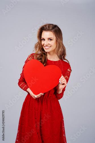 Leinwanddruck Bild Smiling woman holding a big, red heart