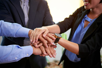 Cropped image of business team stacking hands to express unity and improve communication
