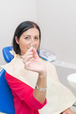 Woman patient sitting on the chair showing dental implant at the dental office - 246656165