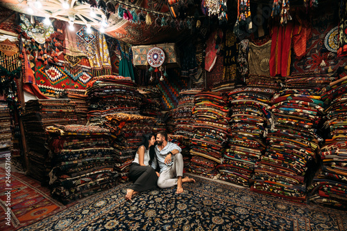 Leinwandbild Motiv Couple having fun. Couple in love in Turkey. Man and woman in the Eastern country. Gift shop. A couple in love travels. Persian shop. Tourists in store. Oriental carpet. Cappadocia. Morocco