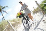 Super smily young woman walking with flower adorned bicycle on beachy path - 246674957