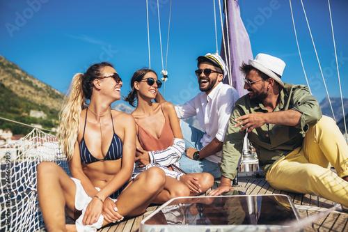 Leinwandbild Motiv Smiling friends sailing on yacht. Vacation, travel, sea, friendship and people concept