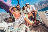 Smiling friends sailing on yacht. Vacation, travel, sea, friendship and people concept - 246700198
