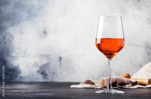 Trendy food and drink, orange wine in glass, gray table background, space for text, selective focus - 246712184