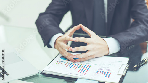 successful businessman is considering the financial policy of the company sitting behind a Desk