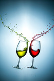 Two Types of Colorful Red and Light Yellow Wine Splashes Poured Out from Glasses Against Bluish Background. Short Flash Duration for Freezing Motion Used. Vertical Shot