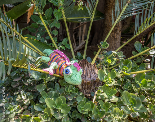 A fake chameleon in a shrub in the garden concept fake image in landscape format with copy space