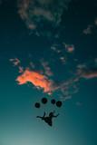 Spensieratezza nell'aria rappresentata da una ragazza che vola con dei palloncini nel cielo al tramonto - 246773956