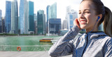 fitness, sport and people concept - happy woman listening to music in earphones over singapore city marina background