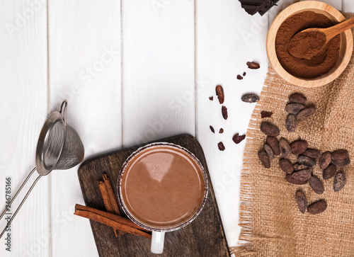 fototapeta na ścianę Hot chocolate in the cup, cocoa beans and powder on the white wooden table