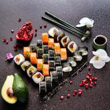 Fototapeta Maki - Sushi rolls set served on black stone slate on dark background © Maksim Shebeko