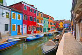 Burano island picturesque street with small colored houses in row, windows, doors and water canal with fisherman boat. Venice Italy