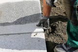 Construction worker laying cobblestones, paving stones - 246810945
