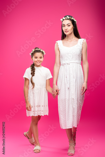 Leinwandbild Motiv beautiful happy mother and daughter in white dresses and floral wreaths holding hands and smiling at camera on pink