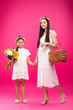 Leinwandbild Motiv beautiful happy mother and daughter in white dresses holding bouquet and picnic basket on pink