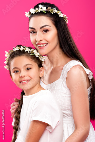 Leinwandbild Motiv beautiful happy mother and daughter in white dresses and wreaths smiling at camera isolated on pink