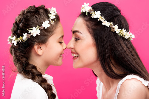 Leinwandbild Motiv side view of happy mother and daughter in white dresses and floral wreaths isolated on pink